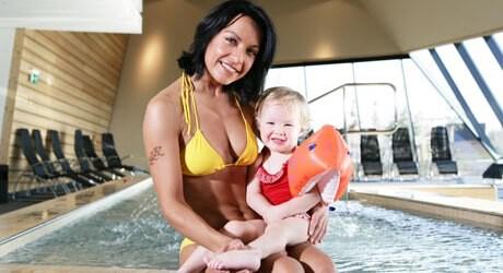 Foto von einem Baby mit Schwimmflügel und seiner Mutter