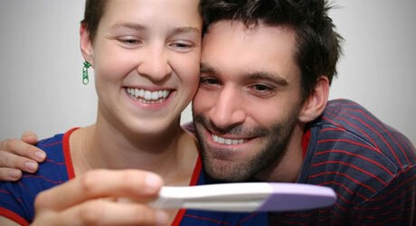 Foto von einem Paar welches einen Schwangerschaftstest ansieht