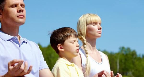 Eltern-Kind-Yoga macht einem Kleinkind sowie Mutter und Vater Spaß