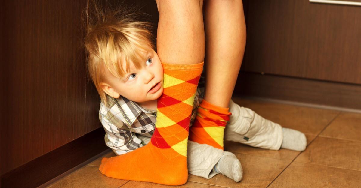 Kleinkind versteckt sich hinter Beinen