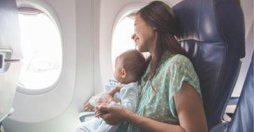 Baby sitzt am Schoß der Mutter und schaut aus Flugzeugfenster