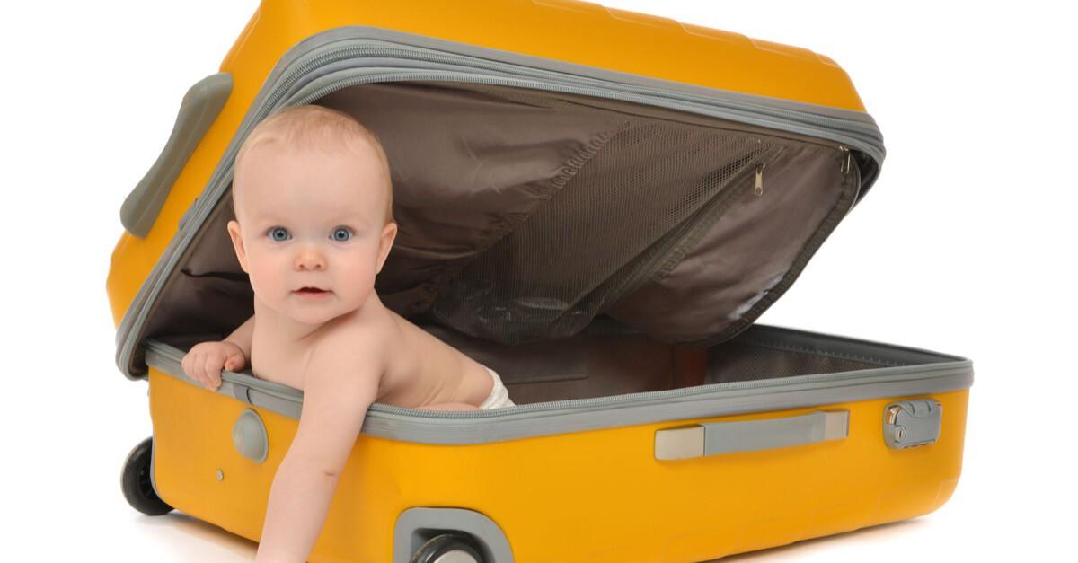 Baby schaut aus gelbem Koffer