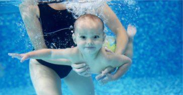 Baby unter Wasser wird von Mutter gehalten