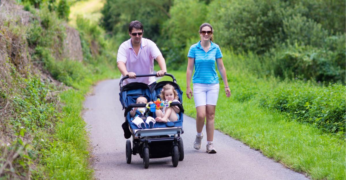 Familie wandert mit Zwillingskinderwagen