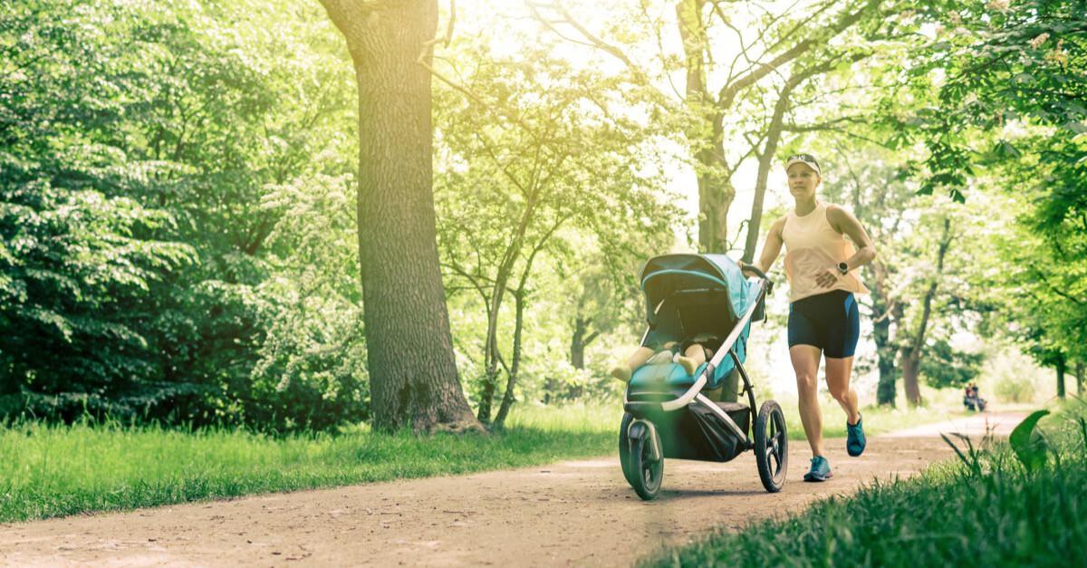 Frau joggt mit Kinderwagen in Park