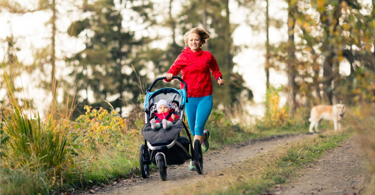 Frau läuft mit Kinderwagen im Wald