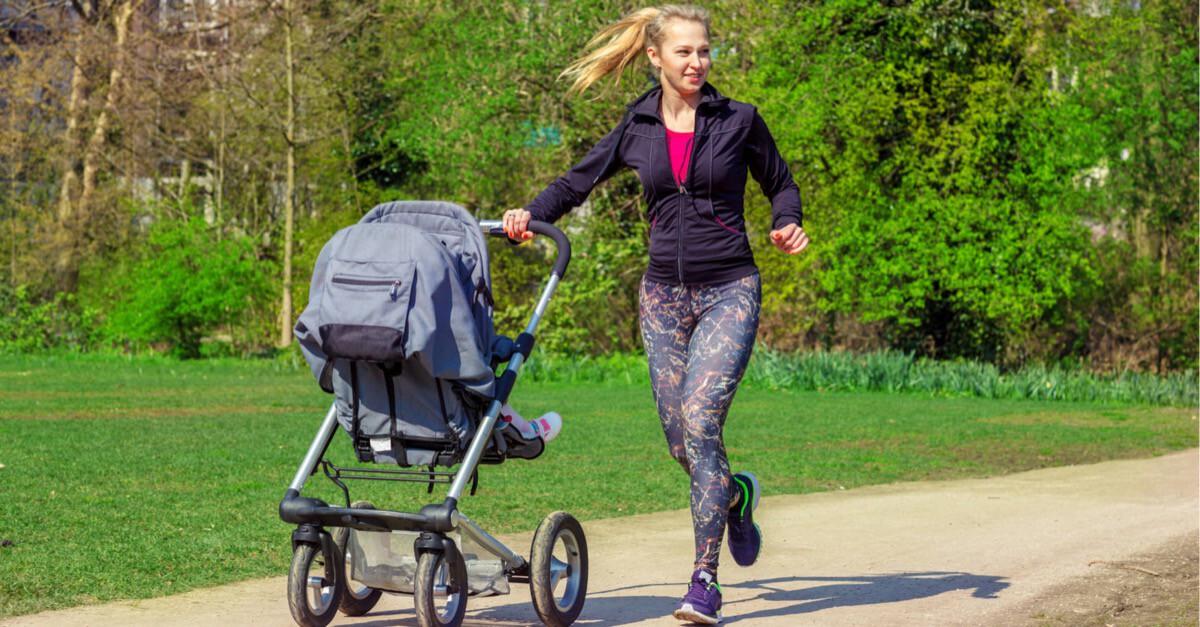 Frau läuft mit Buggy im Park