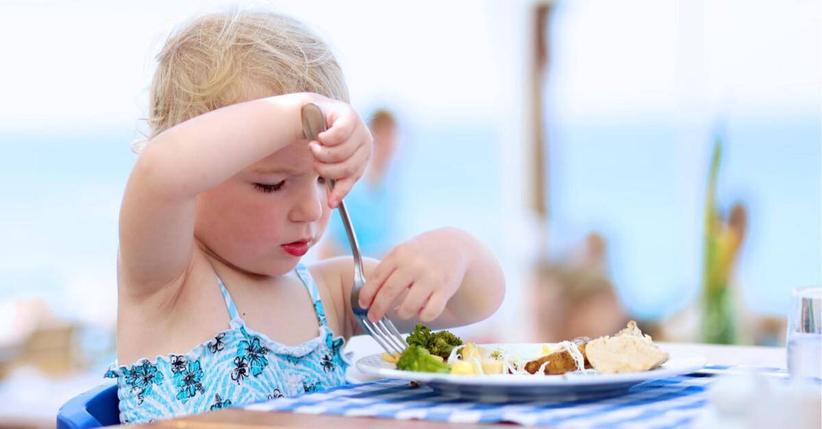 kleines Mädchen isst am Strand