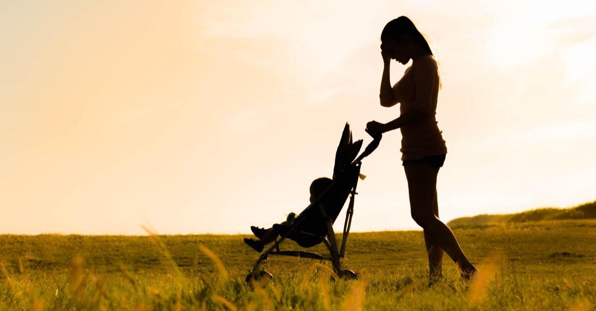 Mutter mit Kinderwagen hält sich Hand an den Kopf
