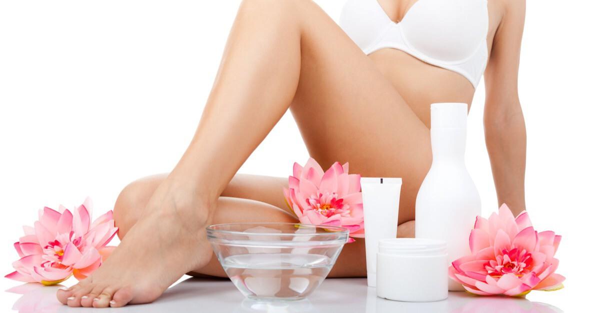 weibliche Beine mit Kosmetikartikeln und Blüten
