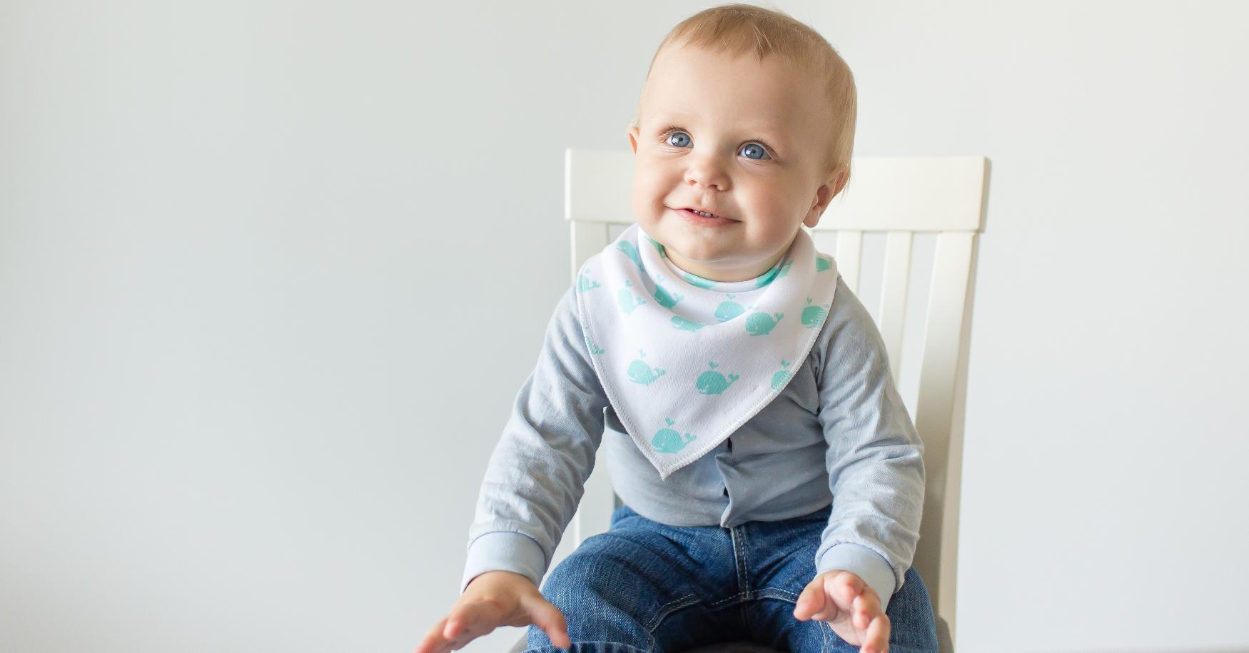 Baby mit Lätzchen sitzt auf Hochstuhl