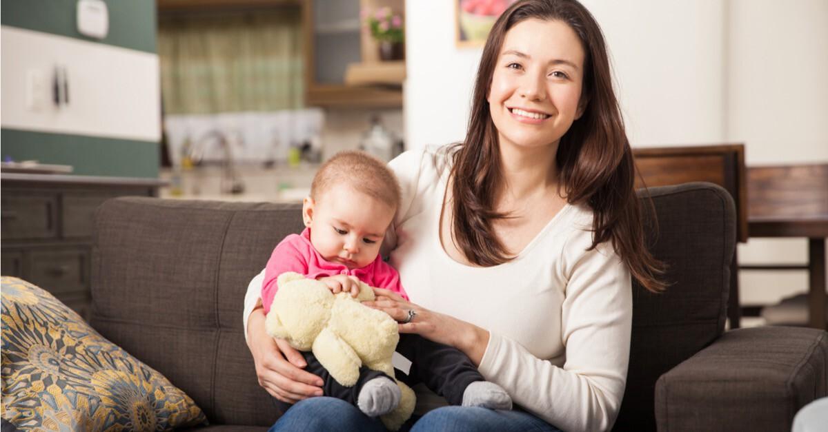 Mutter mit Baby auf couch zu Hause