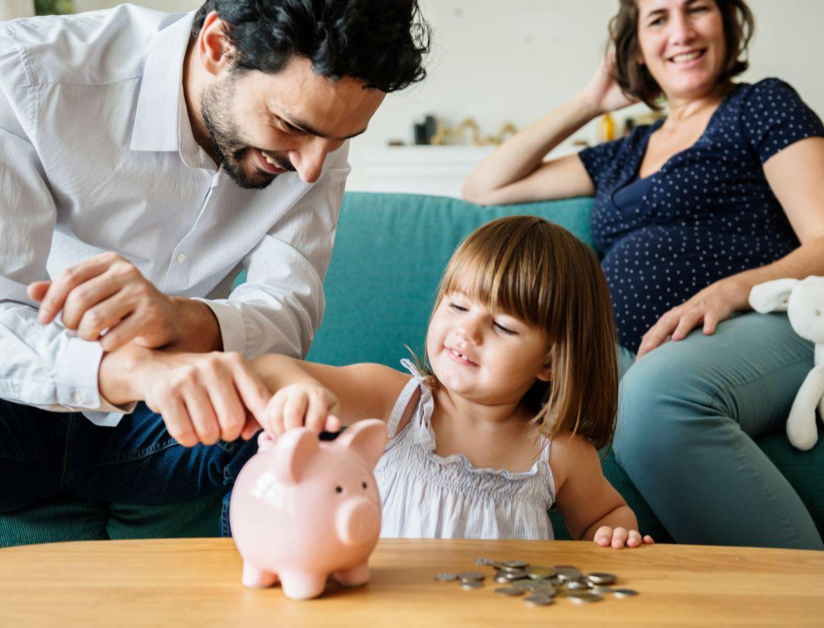 Familie schmeißt Geld in Sparschwein
