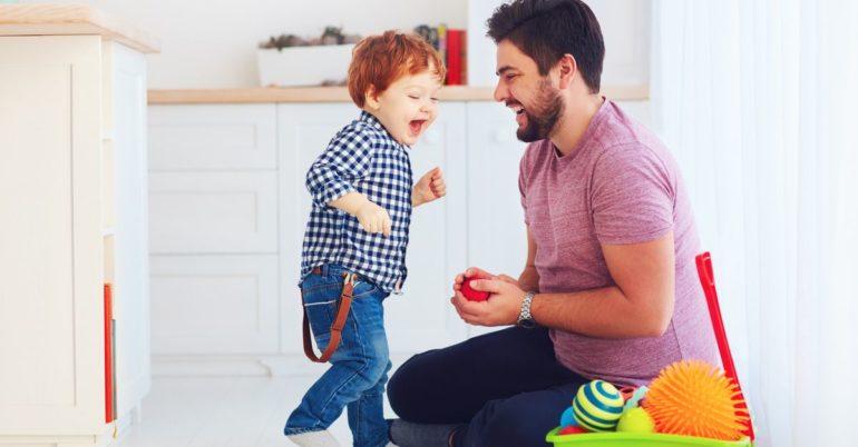Kleinkind spielt mit Vater Ball