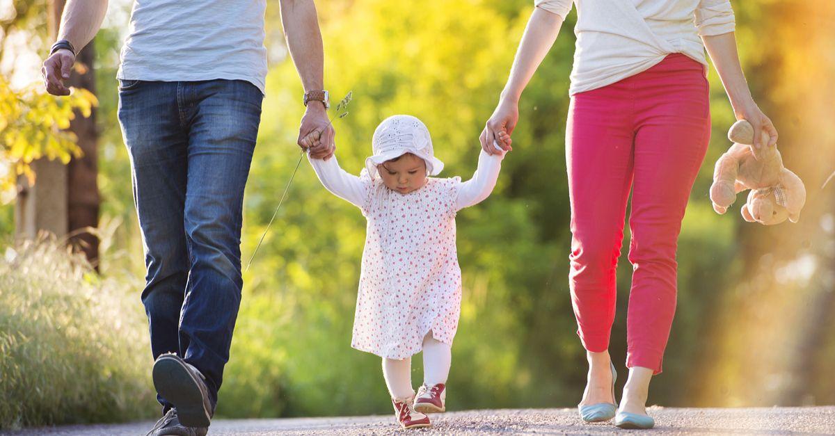 Junge Eltern spazieren mit kleinem Mädchen