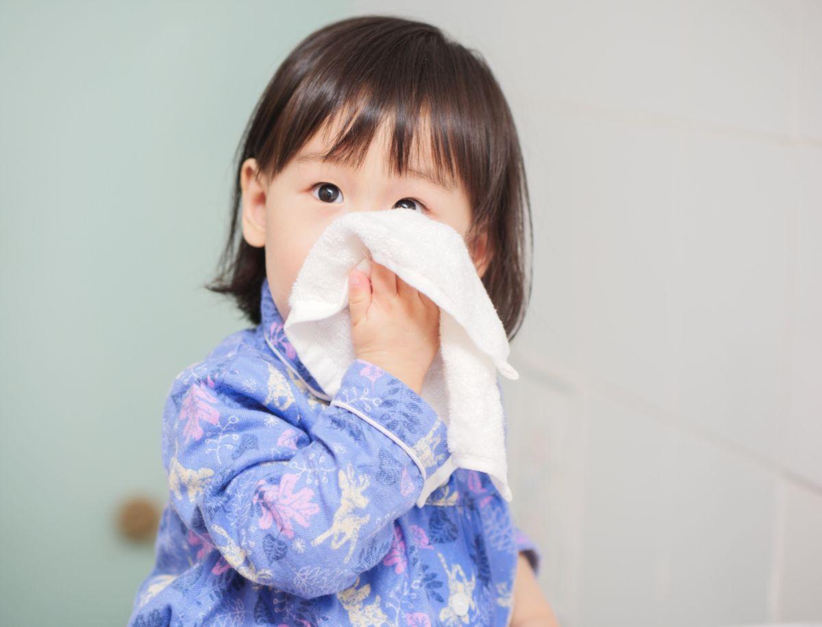 Kleines Mädchen putzt die Nase