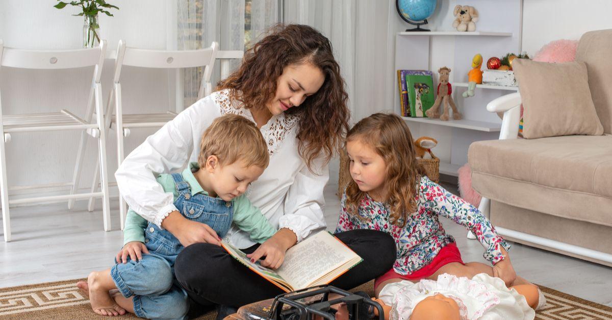 Kindermädchen mit Kindern am Lesen