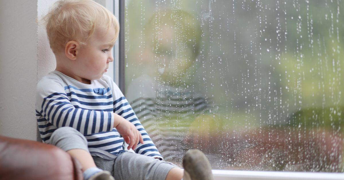 Kleinkind schaut aus Fenster bei regen