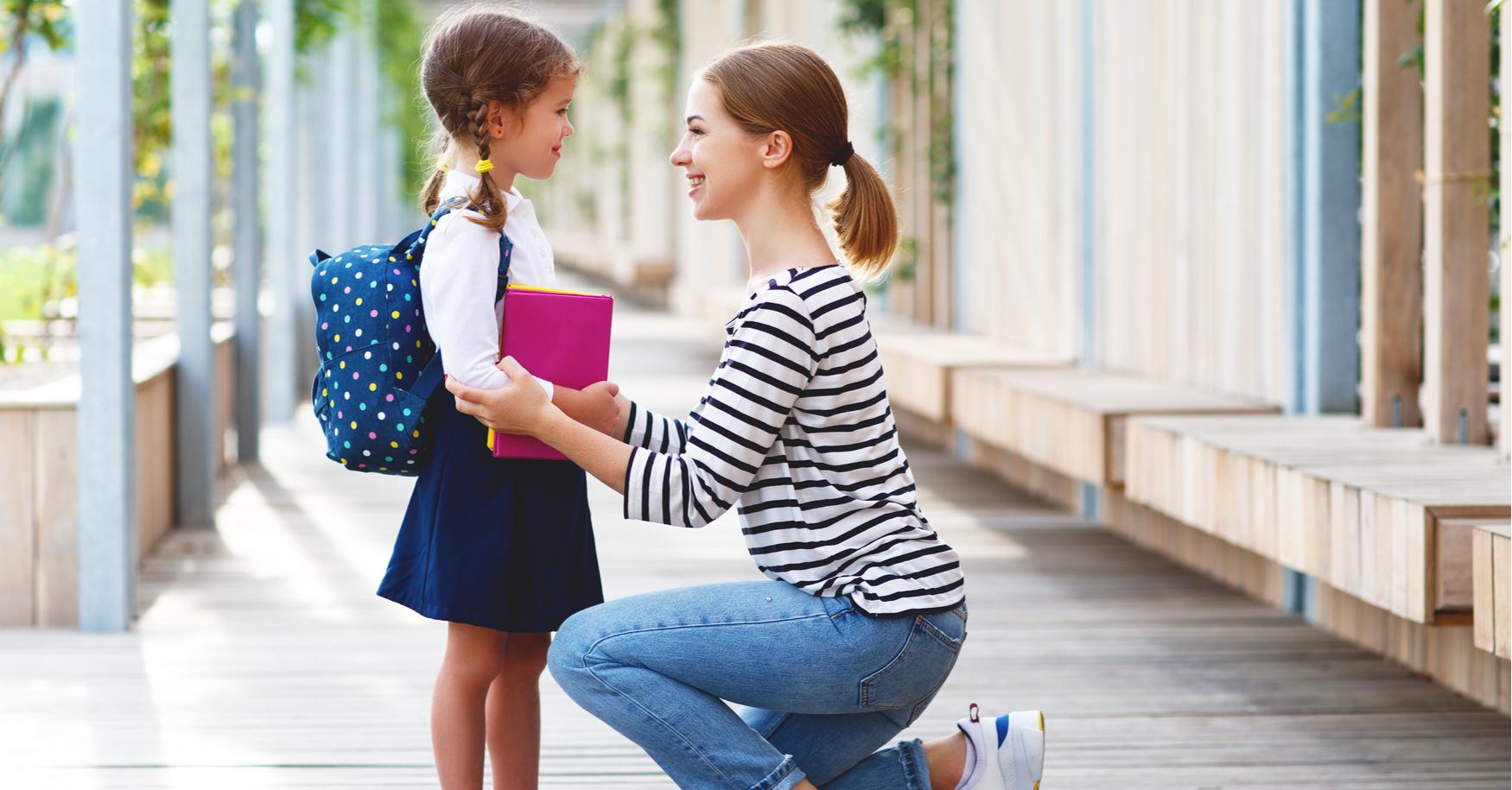 Mama bringt Kind zum ersten Schultag