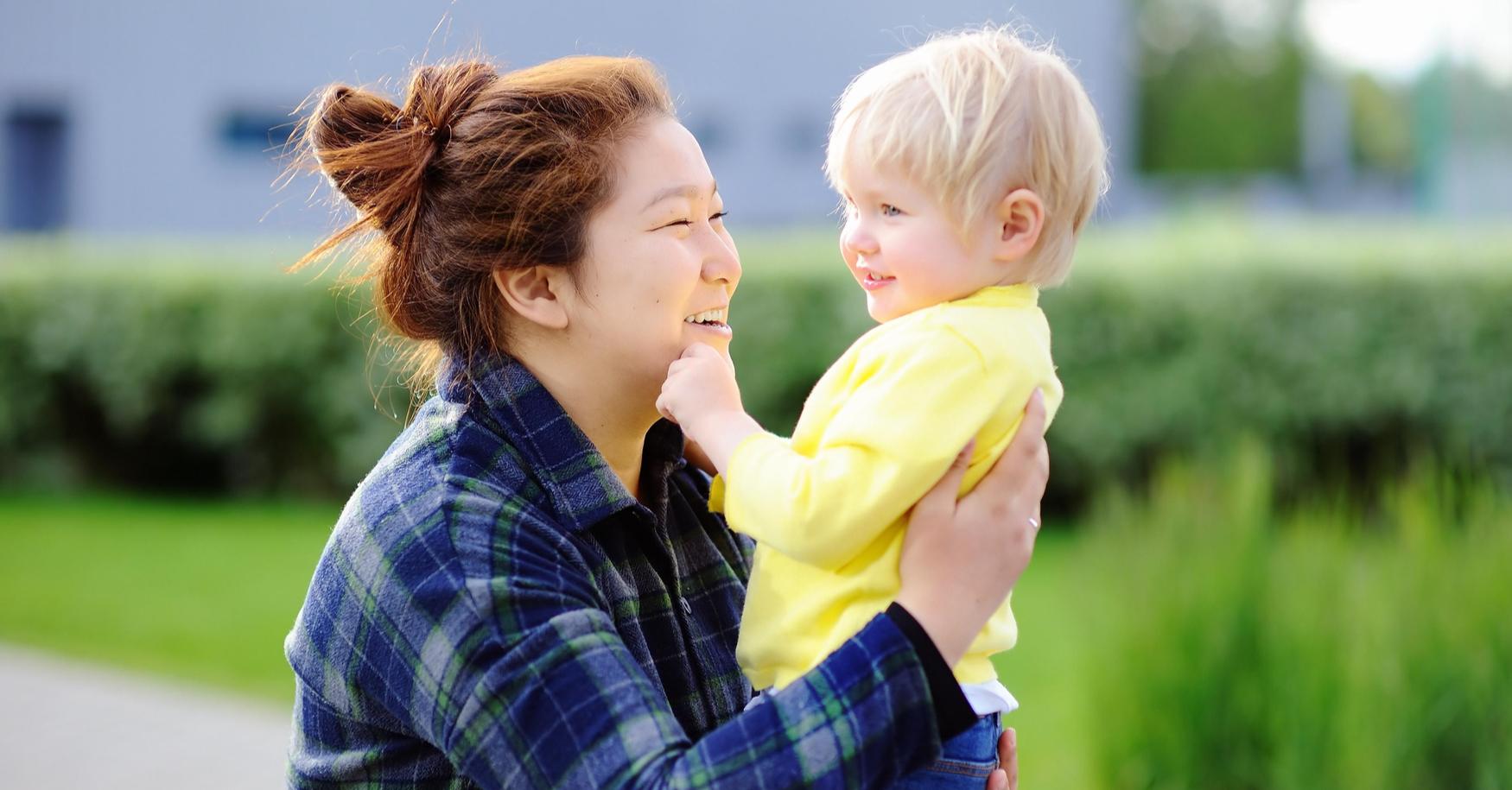 Asiatische Frau lacht mit Kleinkind