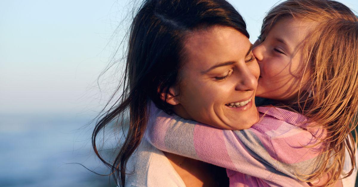 Mutter und Tochter umarmen sich am Meer