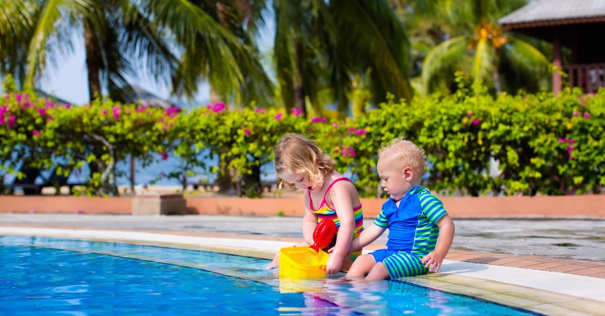 Zwei kleine Kinder sitzen am Pool mit Palmen im Hintergrund
