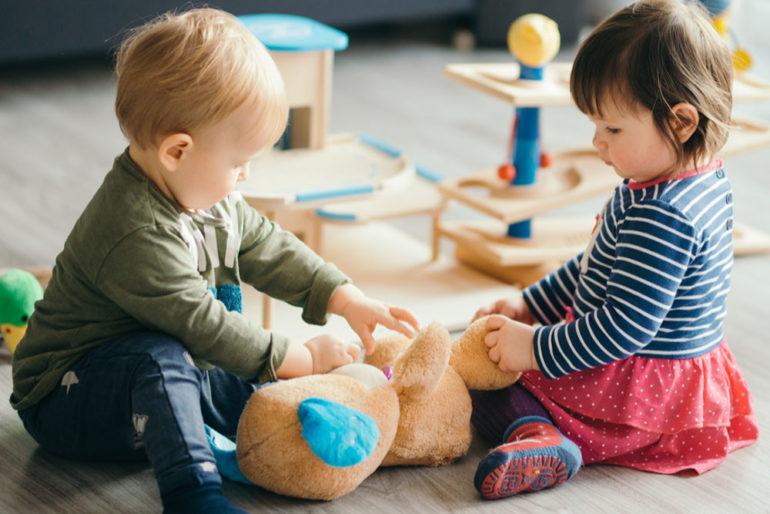 Kleiner Bub und kleines Mädchen spielen in Zimmer